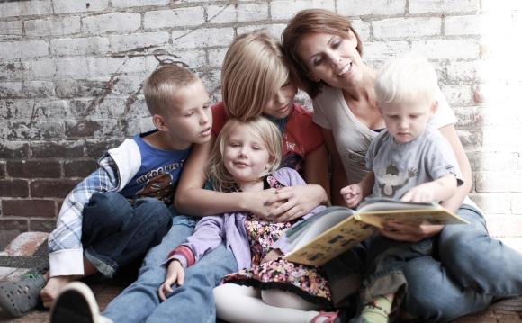 Μητέρα διαβάζει βιβλίο με τα παιδιά της.