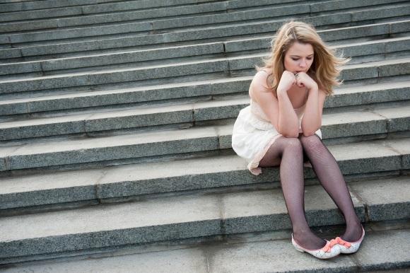 Κάθετε στα σκαλιά και σκέφτεται.