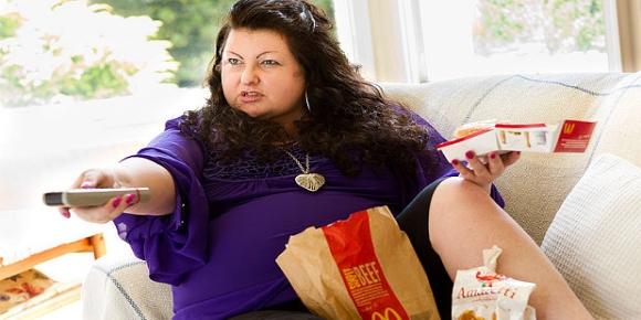 Γυναίκα τρώει και βλέπει τηλεόραση