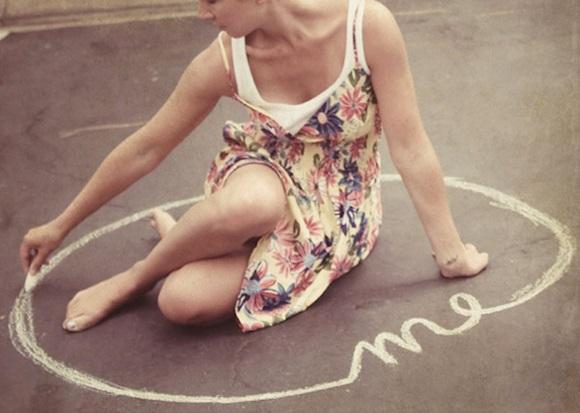 Κοπέλα χαράζει κύκλο με κιμωλία γύρω της.