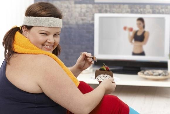 Παχουλή, τρώει ενώ βλέπει γυμναστική στην τηλεόραση.
